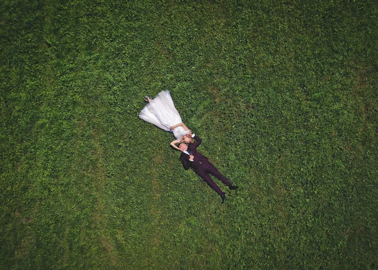 para młoda leżąca na łące z drona